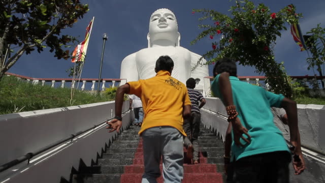 ms people ascend steps towards bahiravokanda vihara buddha statue staring serenely / kandy, central province, sri lanka - weibliche figur stock-videos und b-roll-filmmaterial