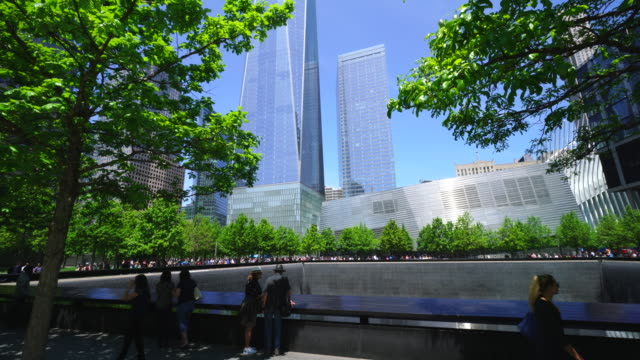 People at 911 Memorial South Pool, which are surrounded by rows of fresh green trees and skyscrapers.