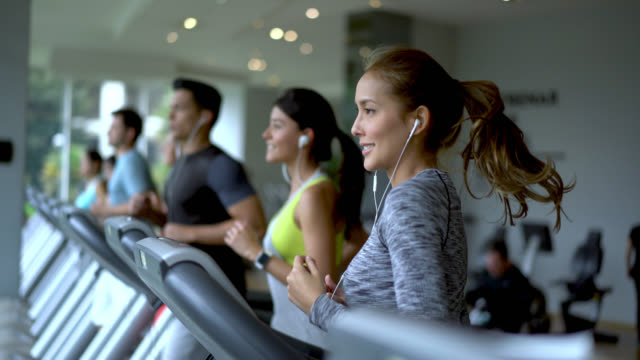 people at a fitness center running on the treadmills looking determined - treadmill stock videos & royalty-free footage