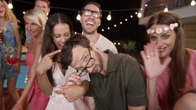 People at a party by the pool at night dancing and posing for a smartphone video