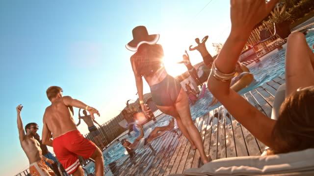 stockvideo's en b-roll-footage met slo mo mensen op een pool party dansen en springen in het zwembad bij zonsondergang - poolparty