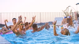 SLO MO DS People at a pool party jumping and dancing in the water at sunset