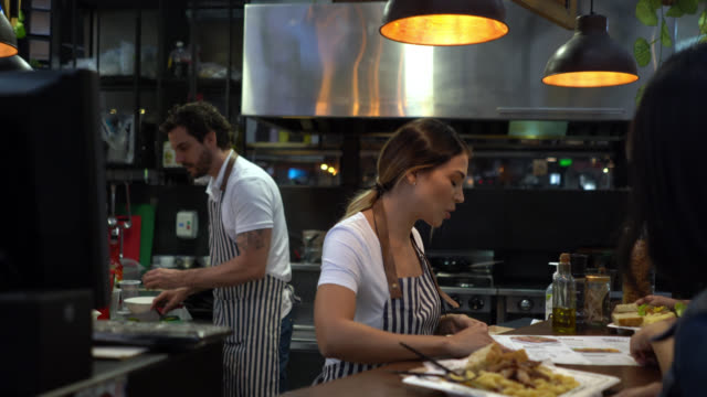 people at a restaurant bar enjoying food and drinks served at the bar counter - bartender stock videos & royalty-free footage