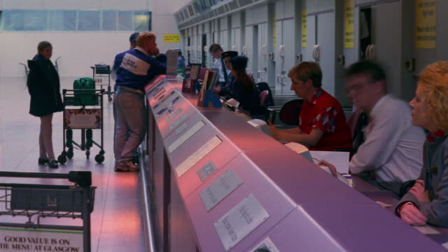 T/L, CU, People at airport check-in counter, England