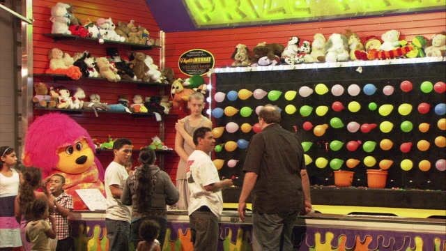 MS People at balloon popping game in arcade game at night / Hartsdale, New York, USA
