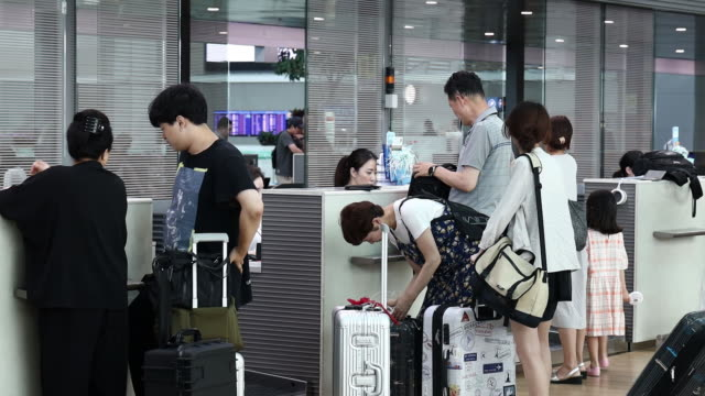 vídeos de stock, filmes e b-roll de people at check-in counter at incheon international airport in incheon, south korea, on wednesday, august 7, 2019. - mala de rodinhas