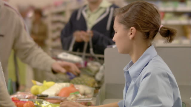 CU People at checkout, cashier scanning products and passing to woman / North Finchley, London, UK