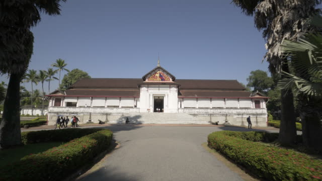 people at famous historic palace museum in city against clear sky on sunny day - luang phabang, laos - off the beaten path stock videos & royalty-free footage