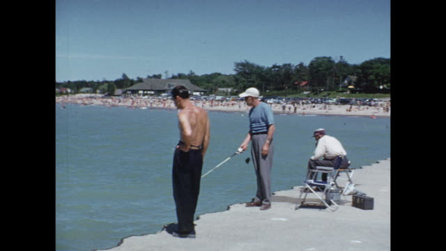1952 MONTAGE People at lake beach, sitting on beach, riding boats, fishing / Grand Bend, Ontario, Canada