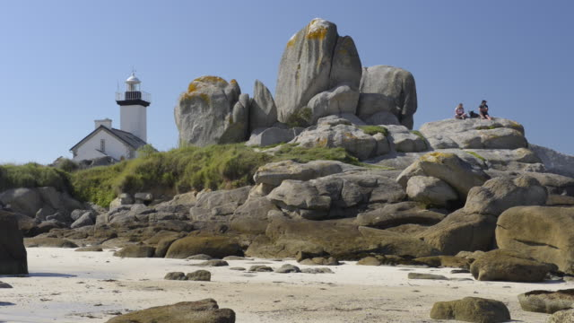 people at lighthouse at rocky coast - finisterra bretagna video stock e b–roll
