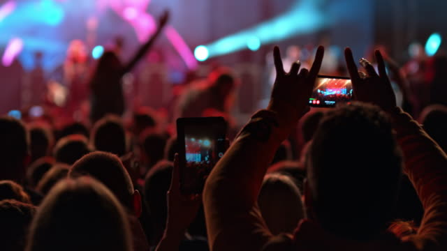 vídeos de stock, filmes e b-roll de people at making smartphone videos of a concert at night - filmando