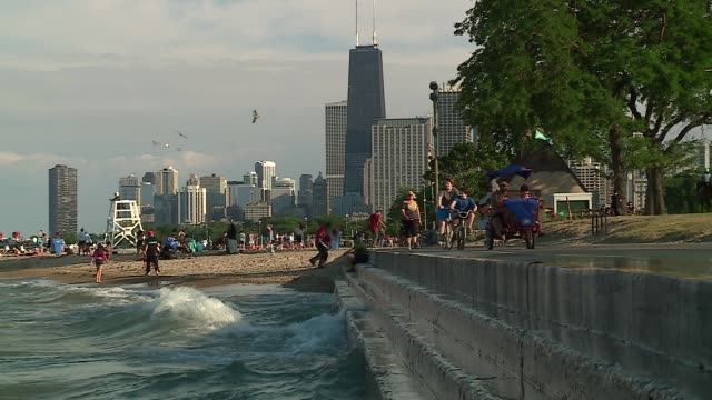 wgn people at north avenue beach and along the chicago lakefront during summer on july 3 2016 - lago michigan video stock e b–roll
