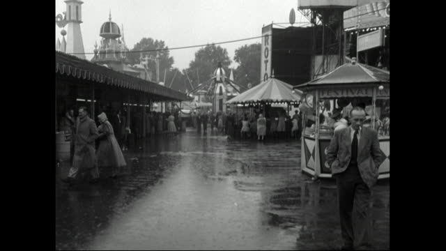b&w people at seaside fairground in the rain; 1951 - 1950 stock videos & royalty-free footage