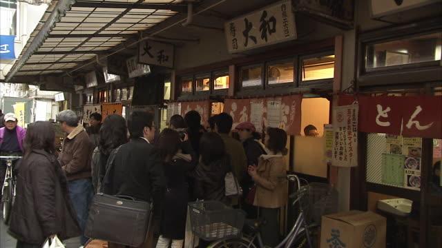 ms pan people at sushi bar at tsukiji fish market, tokyo, japan - 列に並ぶ点の映像素材/bロール