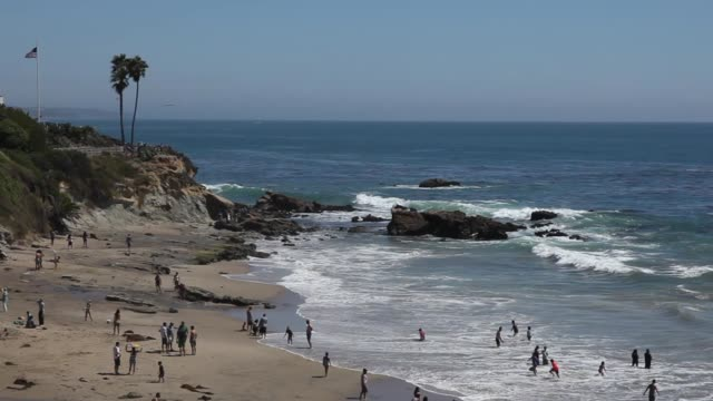 people at the beach of laguna beach in orange county near los angeles, california, usa. the american flag is blowing on the hill next to palm trees - laguna beach california stock videos & royalty-free footage