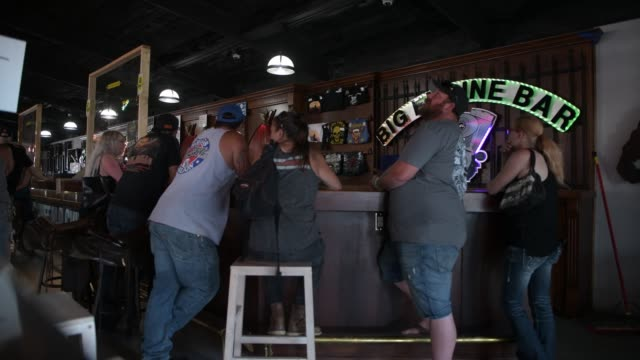 people at the big engine bar at the buffalo chip during the 80th annual sturgis motorcycle rally in sturgis, south dakota on august 9, 2020. while... - veicolo di terra per uso personale video stock e b–roll