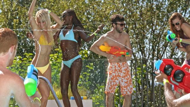 プールで slo mo 人パーティー ダンスと水水の銃からの撮影 - 水鉄砲点の映像素材/bロール