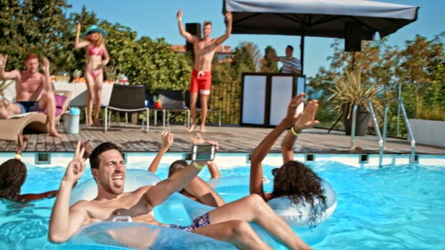 people at the pool party having fun dancing and swimming on a hot day - curly stock videos & royalty-free footage