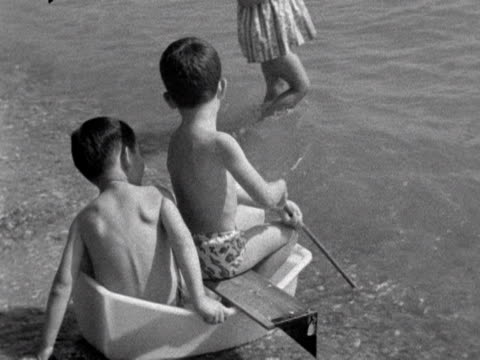 stockvideo's en b-roll-footage met people at the seaside sunbath paddle and swim 1963 - badmuts