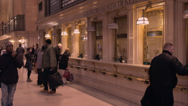 people at the ticket windows of the main concourse in grand central terminal in manhattan - 英字点の映像素材/bロール