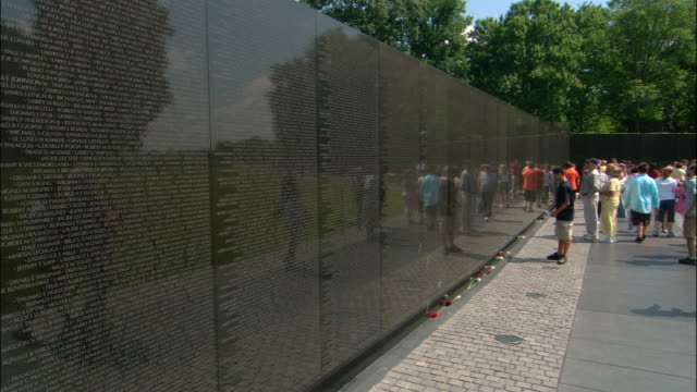 ms, pan, cu people at wall with names of soldiers, vietnam veterans memorial, washington dc, usa - vietnam veterans memorial video stock e b–roll