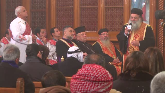 people attend a memorial service as father antonious hanna, representative of coptic patriarch in jordan, receives condolences for the death of... - isis beheading stock-videos und b-roll-filmmaterial