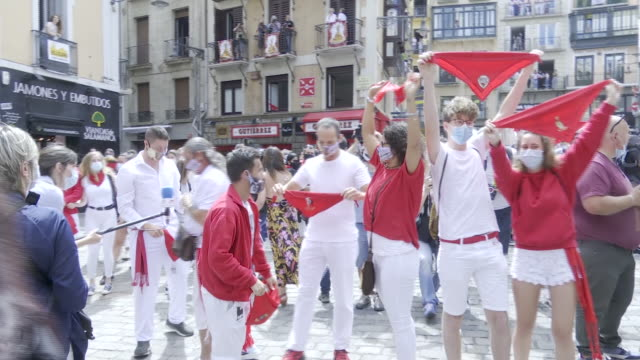 vídeos de stock e filmes b-roll de people attend in front of the ayuntamiento in consistorial square just past noon as the chupinazo to commence the start of the san fermin festival... - meio dia