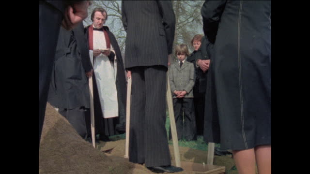 montage people attending funeral /men lowering casket into the ground / united kingdom - begräbnis stock-videos und b-roll-filmmaterial