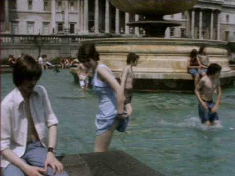 people bathe in fountains at trafalgar square during heatwave 1976 - 1976 stock videos and b-roll footage