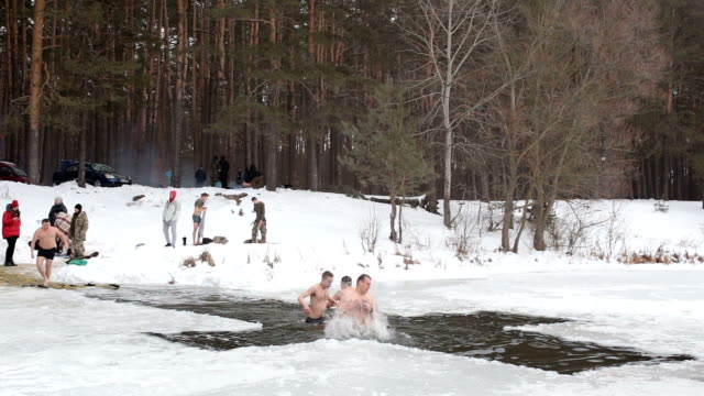 people bathe in the hole during the celebration of epiphany. - taking a bath stock videos & royalty-free footage
