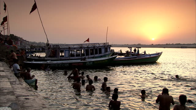 stockvideo's en b-roll-footage met people bathe in the river ganges at sunset. - bedevaart