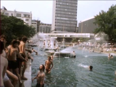 vídeos de stock, filmes e b-roll de people bathe under fountains and in pools during heatwave 1976 - 1976