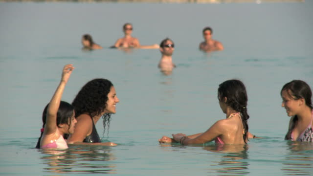 ms selective focus people bathing at dead sea / israel - dead sea stock videos and b-roll footage