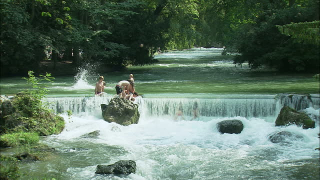 ws people bathing in river in englischer garten (english garden), munich, bavaria, germany - ミュンヘン エングリッシャーガルテン点の映像素材/bロール
