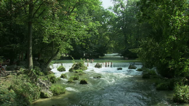 ws ha people bathing in river in englischer garten (english garden), munich, bavaria, germany - ミュンヘン エングリッシャーガルテン点の映像素材/bロール