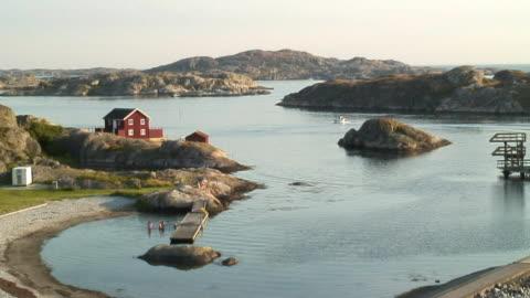 vídeos y material grabado en eventos de stock de ws ha people bathing in sea, boat passing hilly islands in background / sharhamn, tjorn island, bohuslan, sweden - sweden