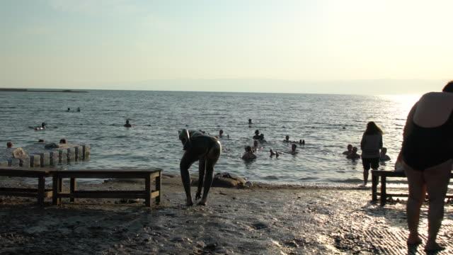 vídeos y material grabado en eventos de stock de people bathing in the dead sea on sunset, jordan - traje de baño de una pieza