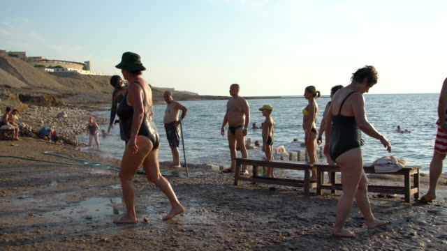 people bathing in the famously hypersaline water of the dead sea on sunset, jordan - swimming costume stock videos & royalty-free footage