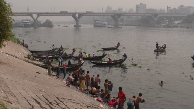 people bathing in the heavily polluted buriganga river in dhaka. - nautical vessel点の映像素材/bロール