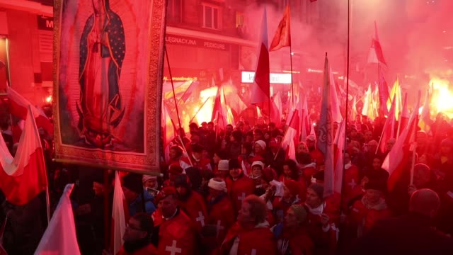 People bearing Polish flags and others holding lit flares participate in the March of Independence during events to mark the 100th anniversary of the...