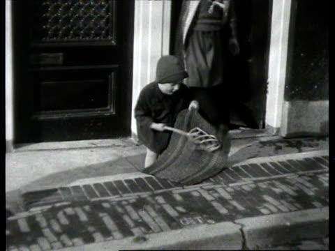 stockvideo's en b-roll-footage met people beating carpets on street and on canal / amsterdam noordholland netherlands - noord holland