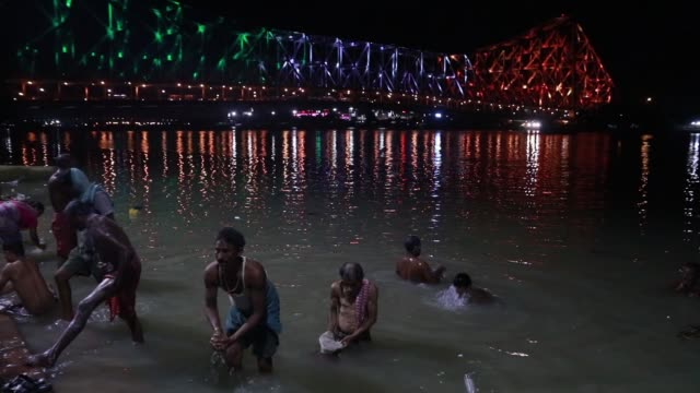 people birth ganges river and back side the howrah bridge illuminated tricolour lights on the eve of 74th independence day celebrations in... - howrah bridge stock videos & royalty-free footage