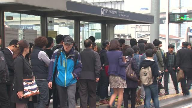 people board a bus in seoul station transportation centre - バス停留所点の映像素材/bロール