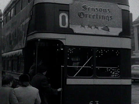 people board a double decker bus in stockton-on-tees which has been decorated with christmas decorations. 1954. - doppeldeckerbus stock-videos und b-roll-filmmaterial