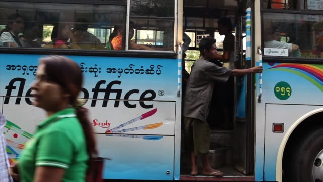 people board buses at a downtown bus station on february 15, 2013 in yangon, burma. myanmar is going through rapid political and economic reforms... - bahnreisender stock-videos und b-roll-filmmaterial
