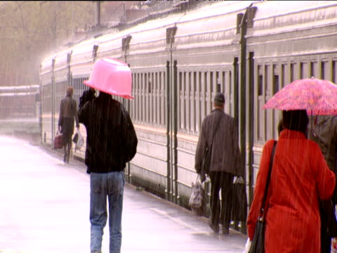 people board train in rain including man with pink plastic bath over his head russia - russian ethnicity stock videos & royalty-free footage