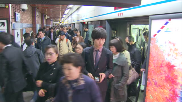 people boarding and disembarking subway trains at seoul station and electronic display - south korea stock videos & royalty-free footage