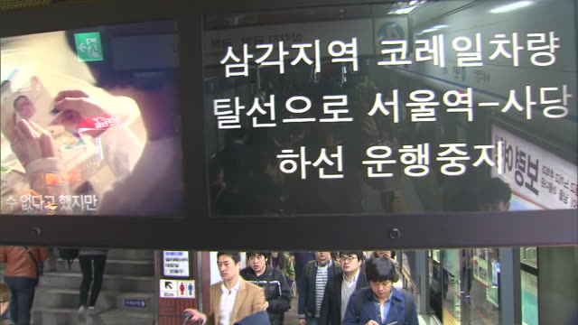 People boarding and disembarking subway trains at Seoul station and electronic display