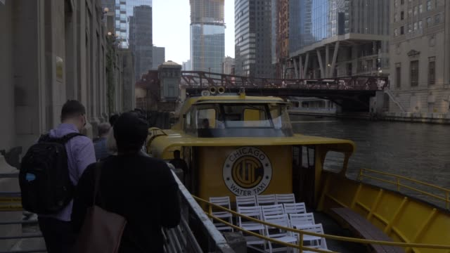 vídeos de stock e filmes b-roll de people boarding river taxi and tall buildings from chicago river, chicago, illinois, united states of america, north america - embarcação comercial