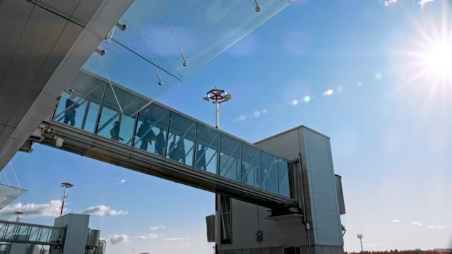 ld people boarding the plane walking across a glass jet bridge in sunshine - airport terminal stock videos & royalty-free footage
